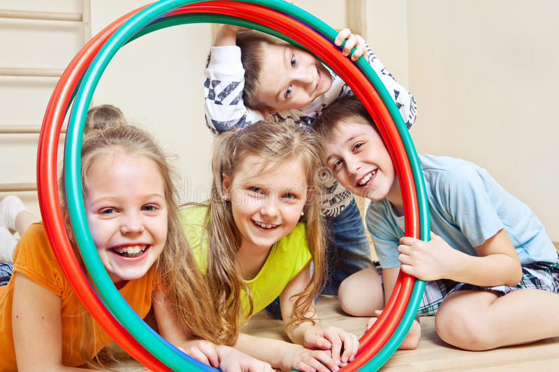 Children with hula hoops. Laughing children holding hula hoops in a school gym stock photography