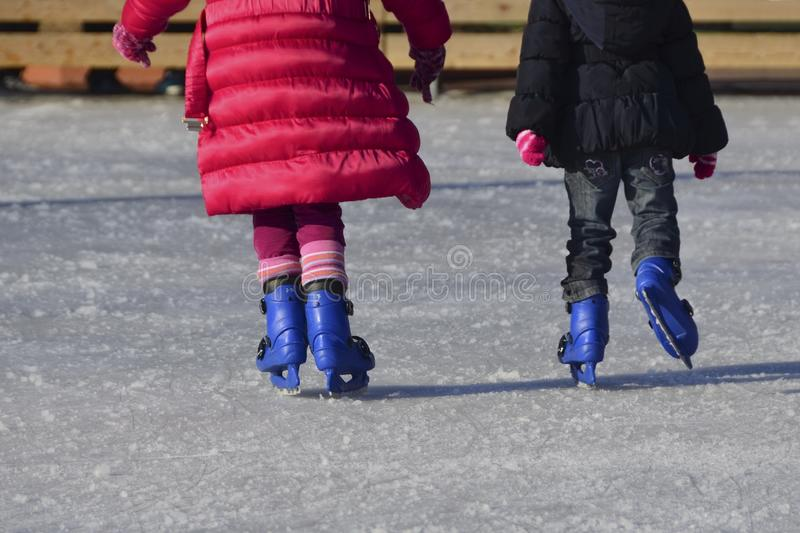 Children ice skating at ice rink outdoor royalty free stock photo