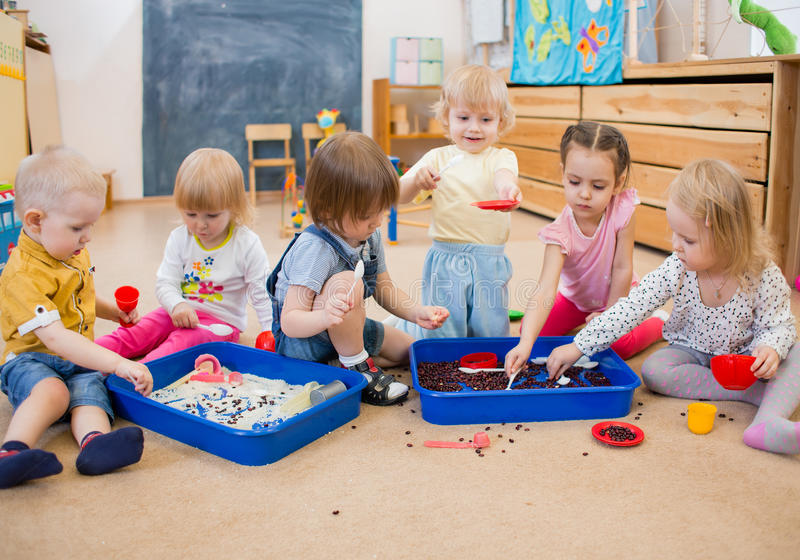 Children improving motor skills of hands in kindergarten. Group of children playing with rice and beans in kindergarten or day care centre stock image