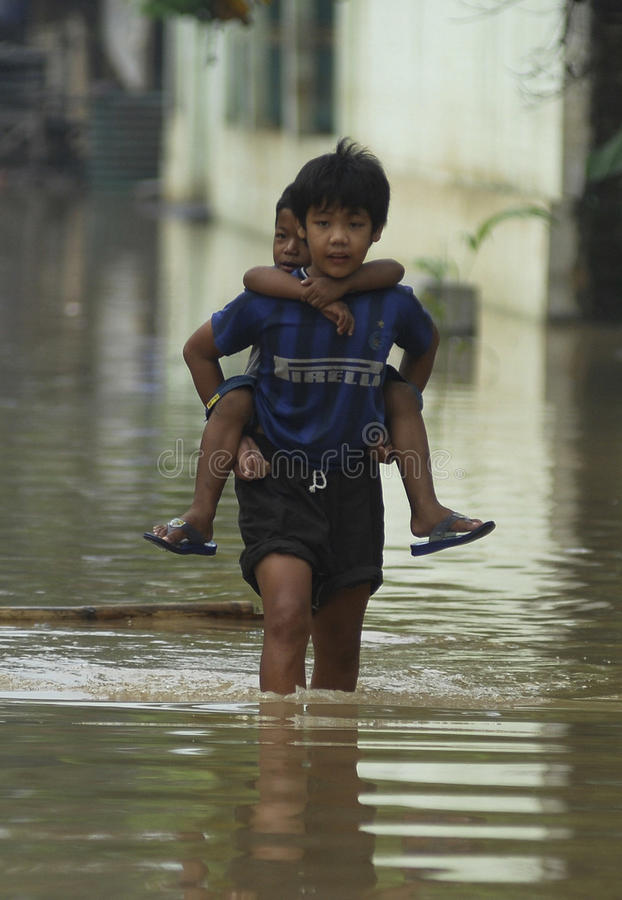 CHILDREN OF INDONESIA POPULATION. A boy carry his little brother through a flooded street of Solo, Java, Indonesia. Of the 237 million inhabitants, almost one stock photo