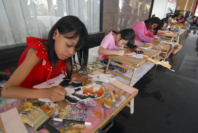 CHILDREN OF INDONESIA POPULATION. Children learn to make shadow puppet in Solo, Java, Indonesia. Of the 237 million inhabitants, almost one-third are under the royalty free stock photography