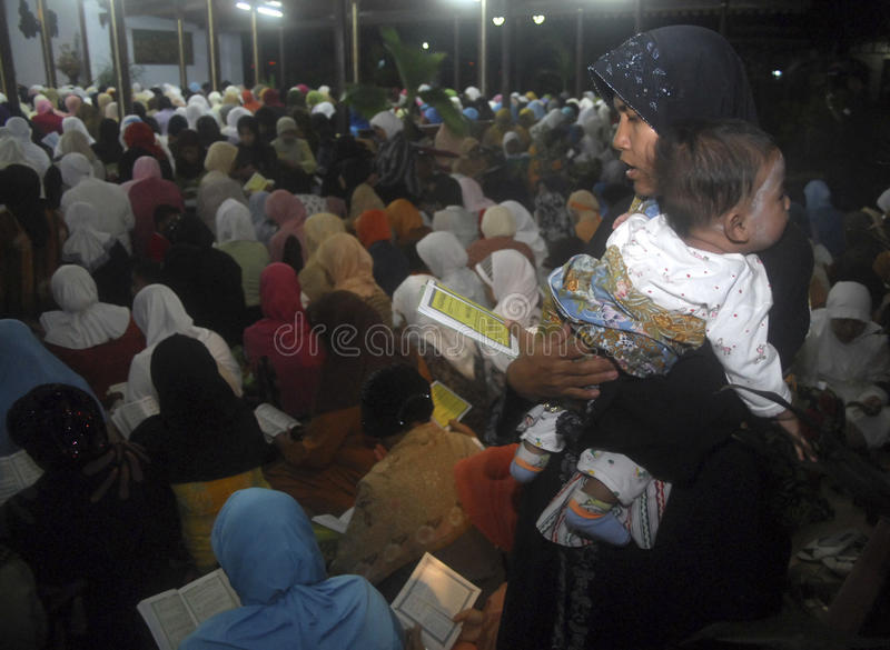 CHILDREN OF INDONESIA POPULATION. A mother carry her child on an Islamic gathering in Solo, Java, Indonesia. Of the 237 million inhabitants, almost one-third are royalty free stock photo