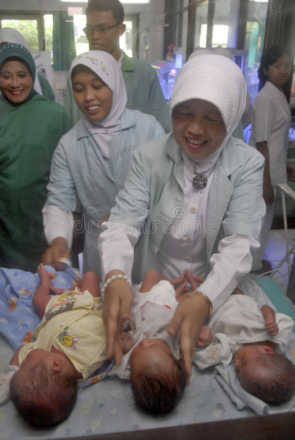 CHILDREN OF INDONESIA POPULATION. A newly born triplets attended at a government hospital in Solo, Java, Indonesia. Of the 237 million inhabitants, almost one stock photo