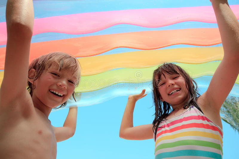 Children with inflatable mattress. A happy, smiling boy and girl, holding a large inflatable air mattress stock image