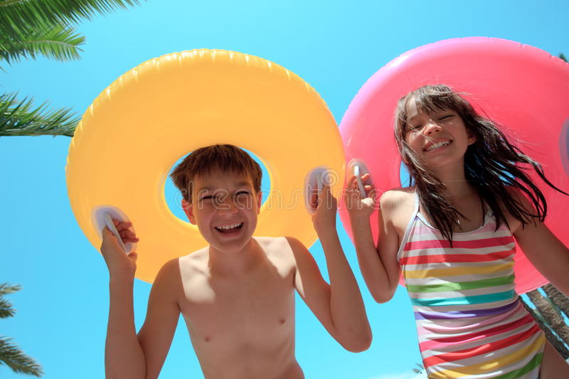 Children with inflatable tubes. A happy and smiling boy and a girl with colorful inflatable swimming tubes or floats stock image