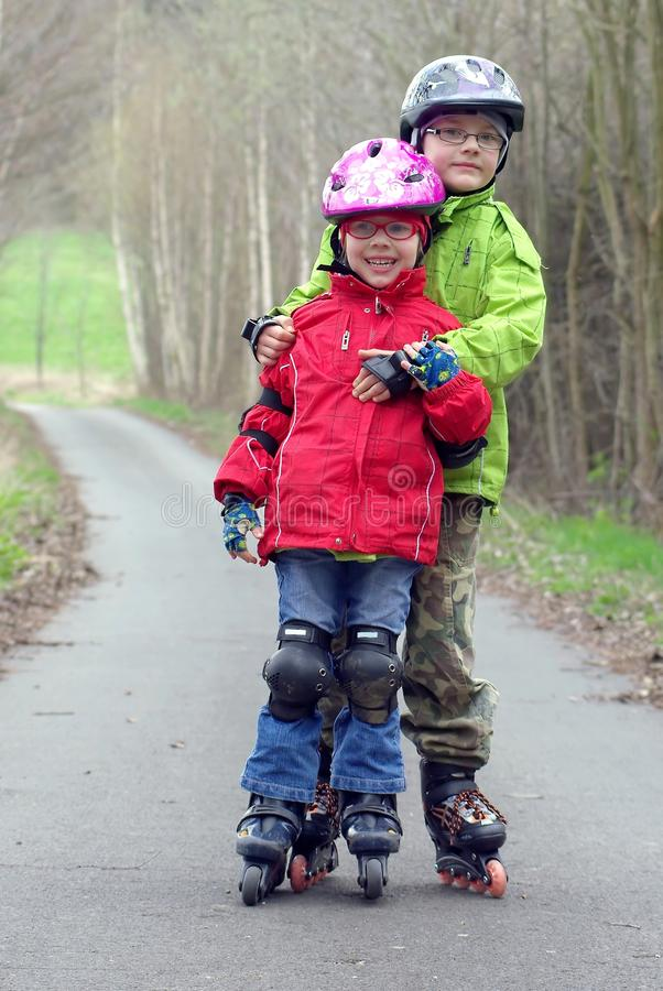 Children on inline skates. Older brother supports her younger sister's inline skates stock photos