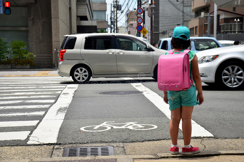 Children japanese girl waiting cross over road at crosswalk traffic road after finished study class at school near Gojo subway st. Ation on July 11, 2015 in royalty free stock photo