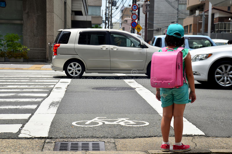 Children japanese girl waiting cross over road at crosswalk traffic road after finished study class at school near Gojo subway st. Ation on July 11, 2015 in royalty free stock photography