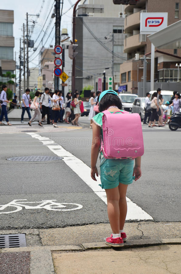 Children japanese girl waiting cross over road. At crosswalk traffic road near Gojo subway station on July 11, 2015 in Kyoto, Japan royalty free stock images