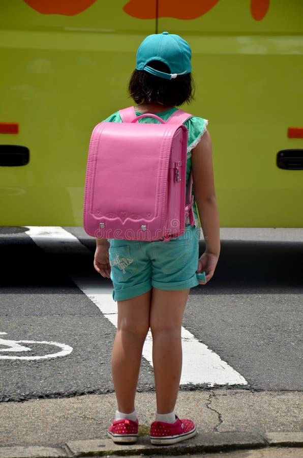 Children japanese girl waiting cross over road. At crosswalk traffic road near Gojo subway station on July 11, 2015 in Kyoto, Japan stock image