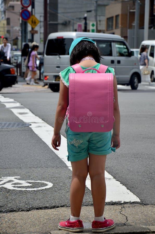 Children japanese girl waiting cross over road. At crosswalk traffic road near Gojo subway station on July 11, 2015 in Kyoto, Japan stock photos