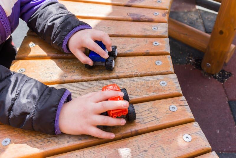Children& x27; jogos exteriores de s no campo de jogos Carros pequenos na criança fotografia de stock