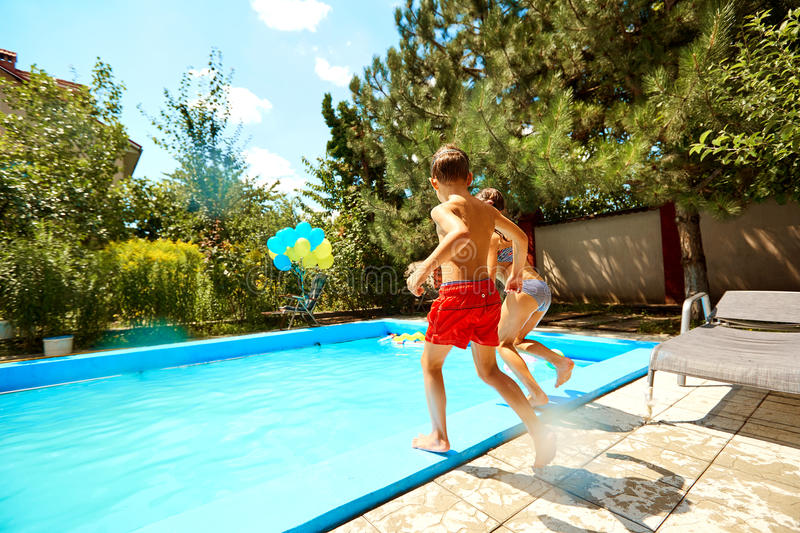 Children jump into the pool in the summer royalty free stock photo