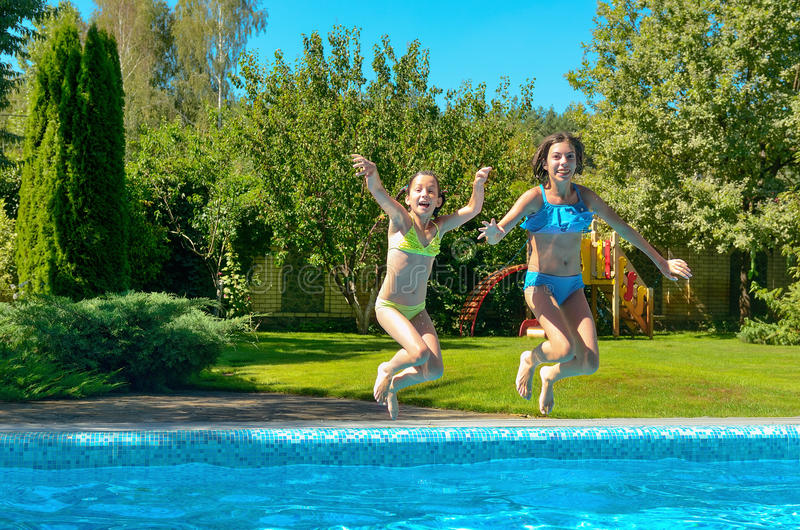 Children jump to swimming pool water and have fun, kids on family vacation. Children jump to swimming pool water and have fun, happy active kids on family stock photography
