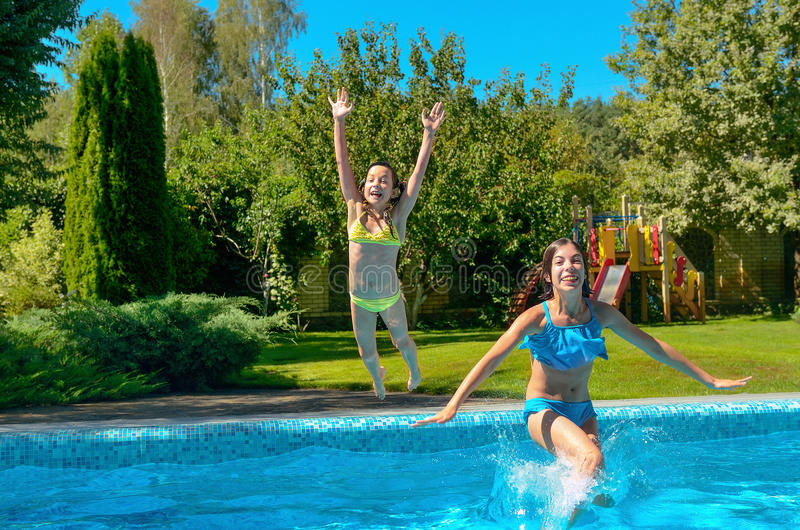 Children jump to swimming pool water and have fun, kids on family vacation royalty free stock image