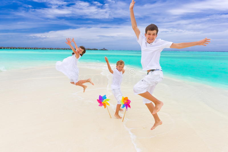 Children jumping on beach stock image