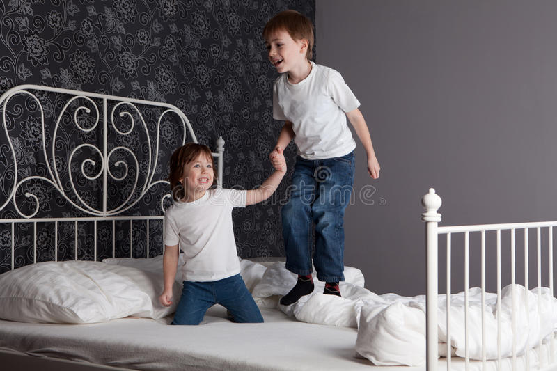Children jumping on bed. Young boy and girl playing and jumping on a bed stock photography