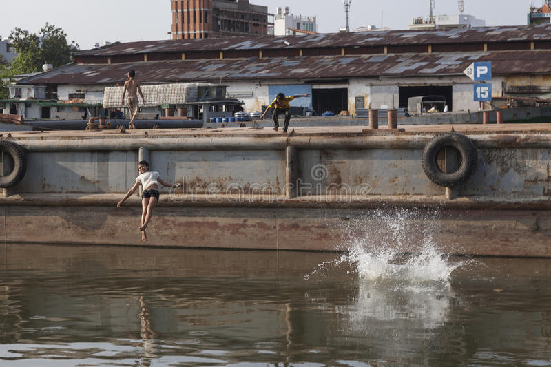 Children jumping in polluted river Saigon. Thanks to indutrial and urban vaste Saigon river is extremly polluted. But children living in the poor districts of Ho royalty free stock photography