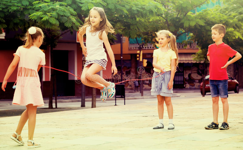 Children with jumping rope at playground. Group of joyful children skipping together with jumping rope on urban playground royalty free stock photography