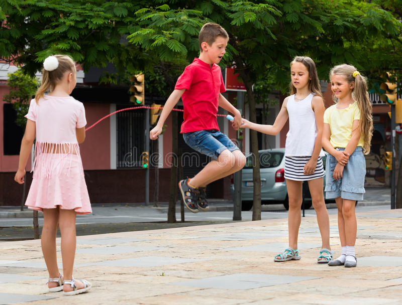 Children with jumping rope at playground. Group of smiling children skipping together with jumping rope on urban playground royalty free stock photography