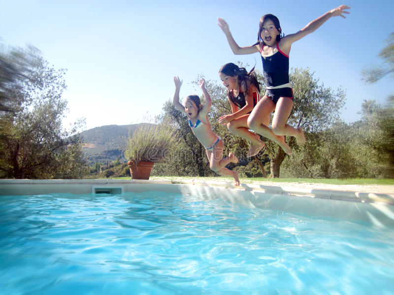 Summer time. Summer scene, three happy children jumping into swimming pool outdoors