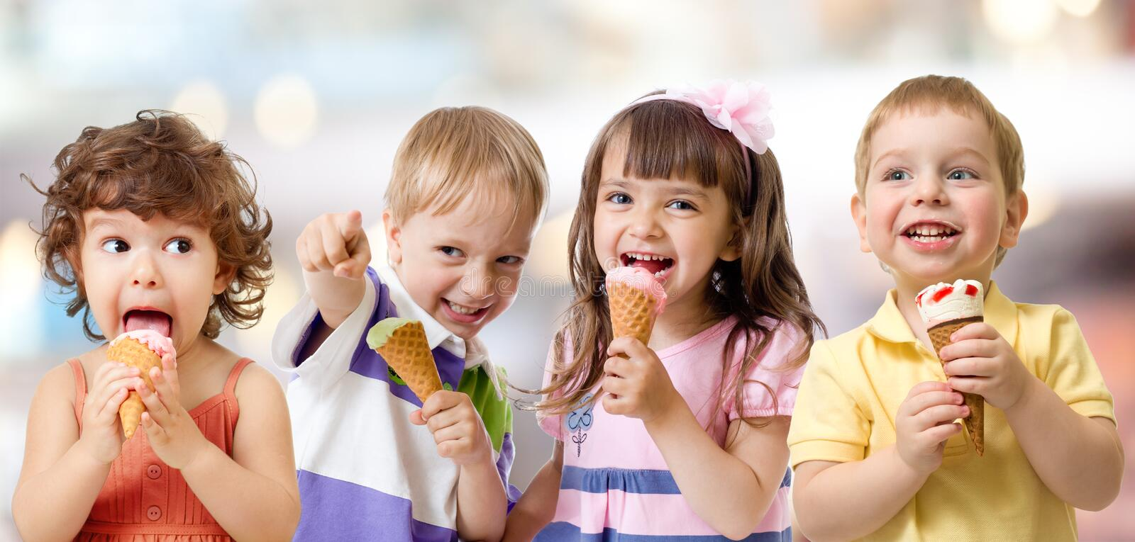 Children or kids group eating ice cream. Funny children group eating ice cream on party stock photos