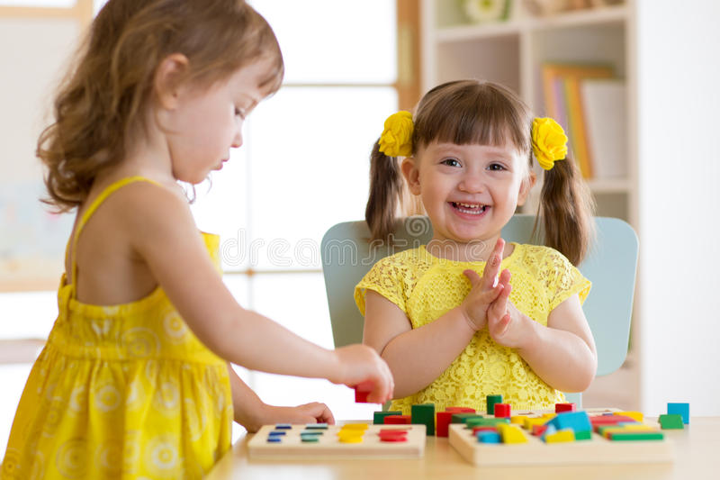 Children kids play with educational toys, arranging and sorting colors and shapes. Learning via experience conception. royalty free stock photography