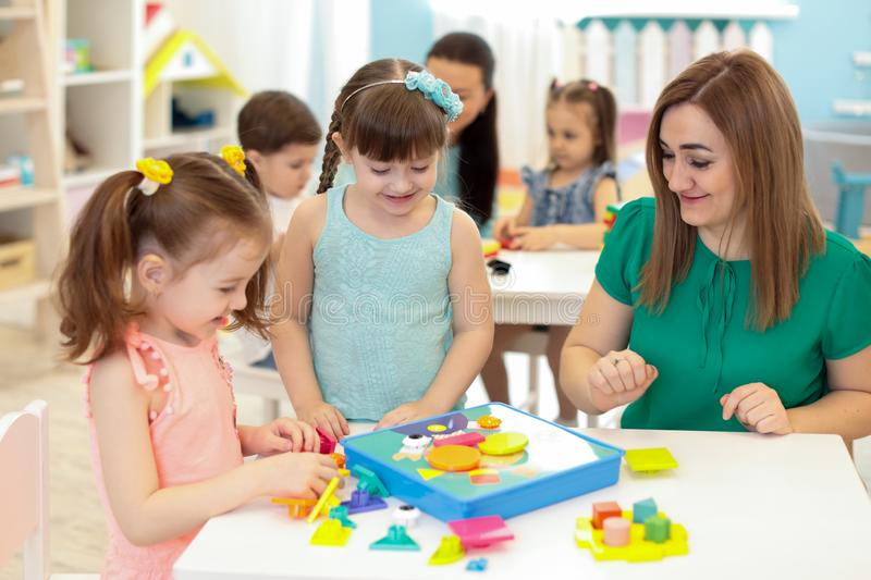 Children kids playing with constructor on table in kindergarten royalty free stock images