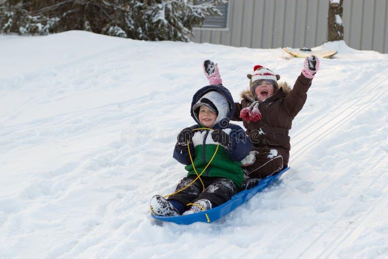 Children kids sledding toboggan sled snow winter royalty free stock photo
