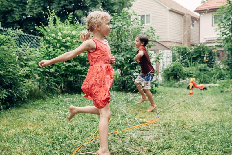 Children kids splashing with gardening hose sprinkler on backyard on summer day royalty free stock image