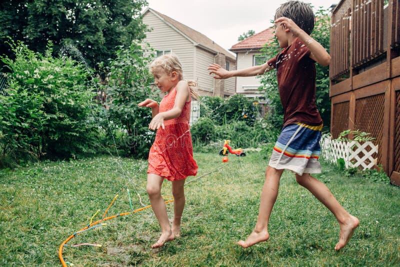 Children kids splashing with gardening hose sprinkler on backyard on summer day stock images