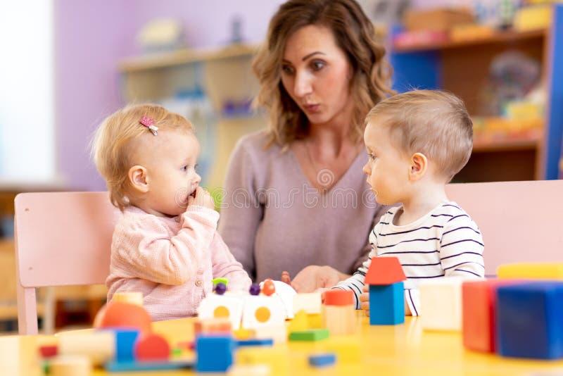 Children in kindergarten. Kids in nursery school. Little girl and boy preschoolers playing with teacher. royalty free stock photo