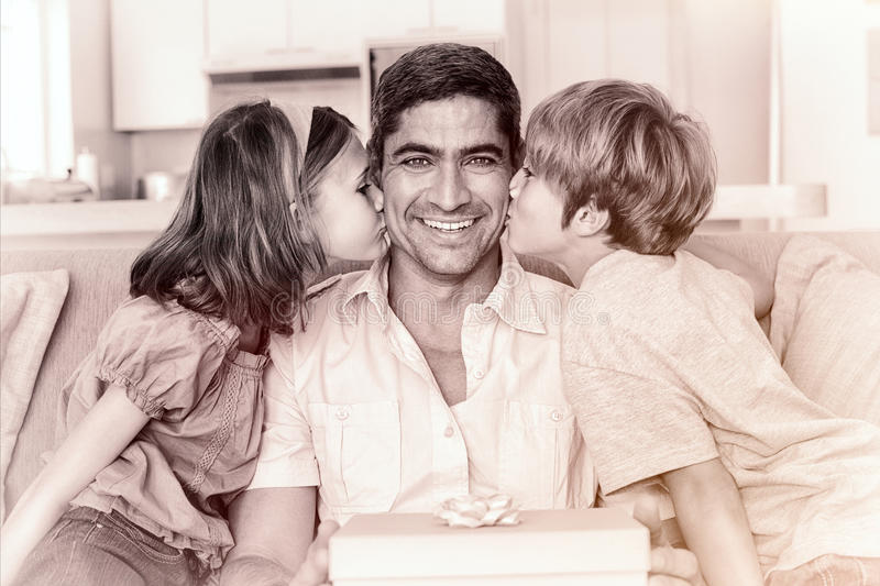 Children kissing on fathers cheeks royalty free stock photo