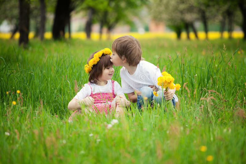 Children kissing in meadow. Two young children kissing in flowery meadow of long grass, girl wearing daisy flower crown royalty free stock image
