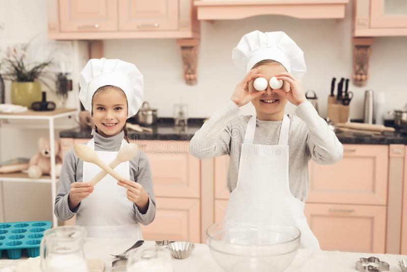 Children in kitchen. Brother is holding eggs and sister is holding spoons. Children in chef`s hats in kitchen. Brother is holding eggs and sister is holding stock image
