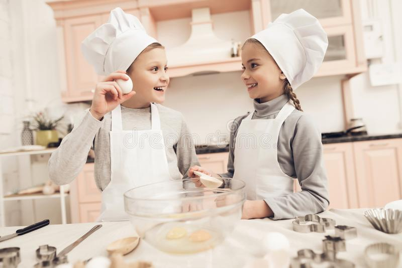 Children in kitchen. Brother is showing sister how he is going to break egg. Children in chef`s hats in kitchen. Brother is showing sister how he is going to stock photos