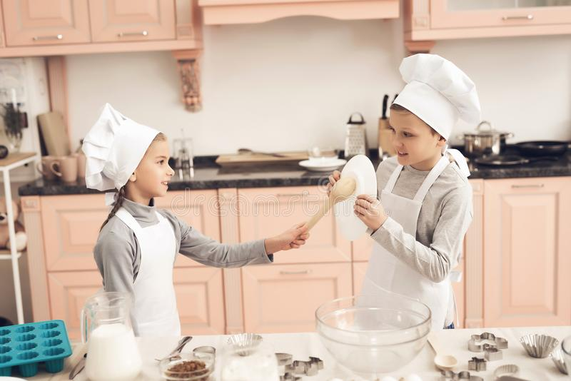 Children in kitchen. Brother and sister are fighting with spoons. Children in kitchen. Brother and sister in chef`s hats are fighting with spoons stock images