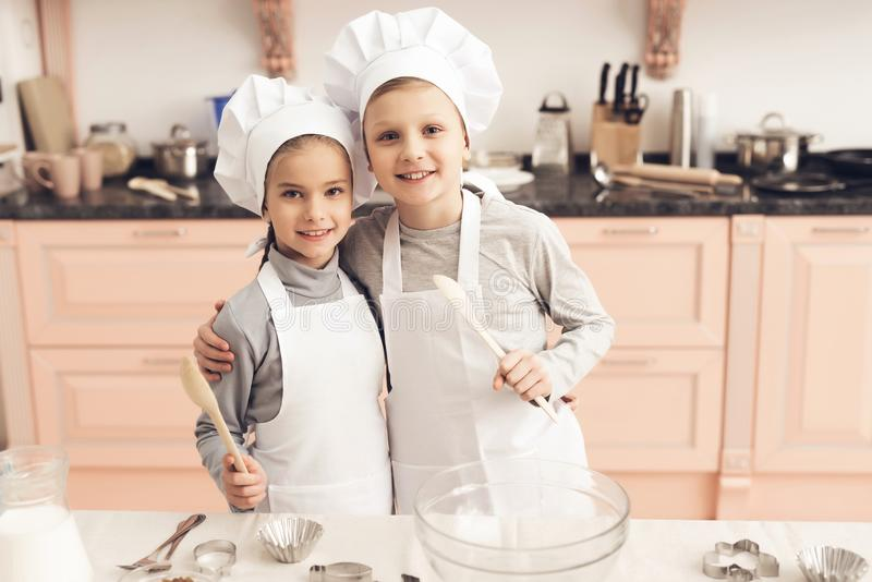 Children in kitchen. Brother and sister are holding spoons. Children in kitchen. Brother and sister in chef`s hats are holding spoons stock image