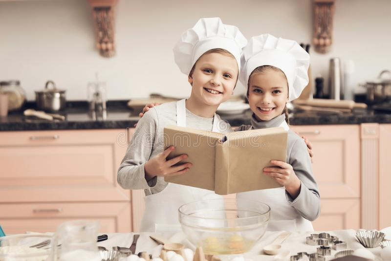 Children in kitchen. Brother and sister are reading cookbook while cooking. Children in chef`s hats in kitchen. Brother and sister are reading cookbook while royalty free stock photos