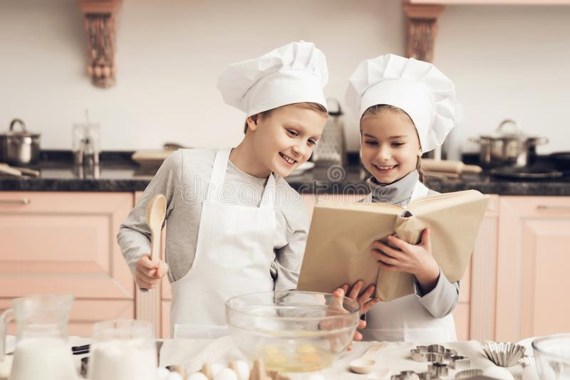 Children in kitchen. Brother and sister are reading cookbook while cooking. Children in chef`s hats in kitchen. Brother and sister are reading cookbook while royalty free stock image