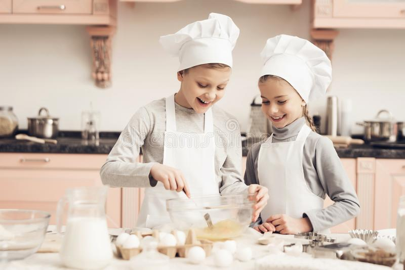 Children in kitchen. Brother and sister are whisking eggs with fork. Children in chef`s hats in kitchen. Brother and sister are whisking eggs with fork stock photo