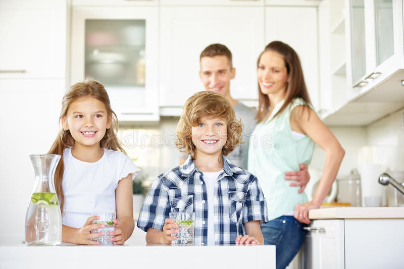 Children in kitchen with fresh water. With limes while parents are watching royalty free stock photo
