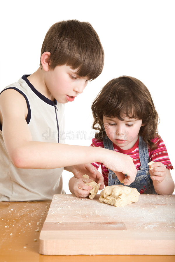 Children in the kitchen making a dough. A children in the kitchen making a dough royalty free stock images