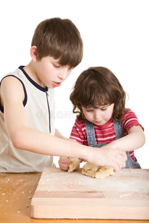 Children in the kitchen making a dough. A children in the kitchen making a dough royalty free stock image