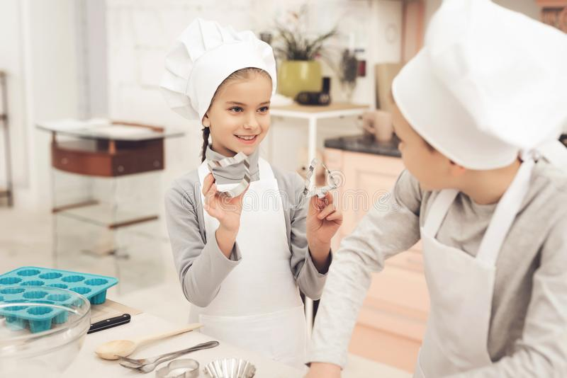 Children in kitchen. Sister is holding baking forms, cat and christmas tree. Children in chef`s hats in kitchen. Sister is holding baking forms, cat and stock photo