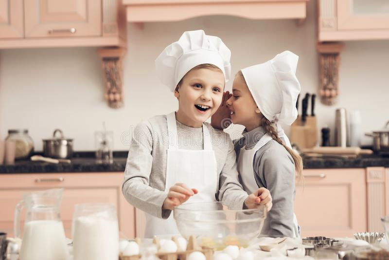 Children in kitchen. Sister is telling brother a secret while cooking. Children in chef`s hats in kitchen. Sister is telling brother a secret while cooking stock images