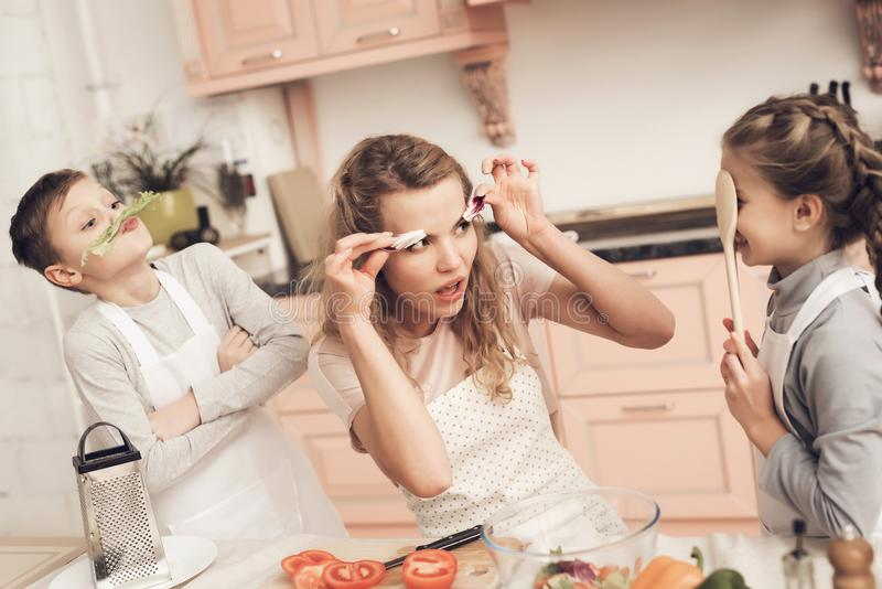 Children in kitchen. Brother and sister are playing with vegetables. Children at kitchen table in kitchen. Brother and sister are playing with vegetables stock photos