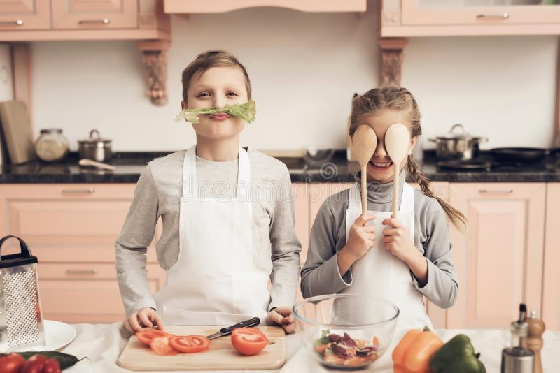 Children in kitchen. Brother and sister are playing with vegetables. Children at kitchen table in kitchen. Brother and sister are playing with vegetables royalty free stock photography