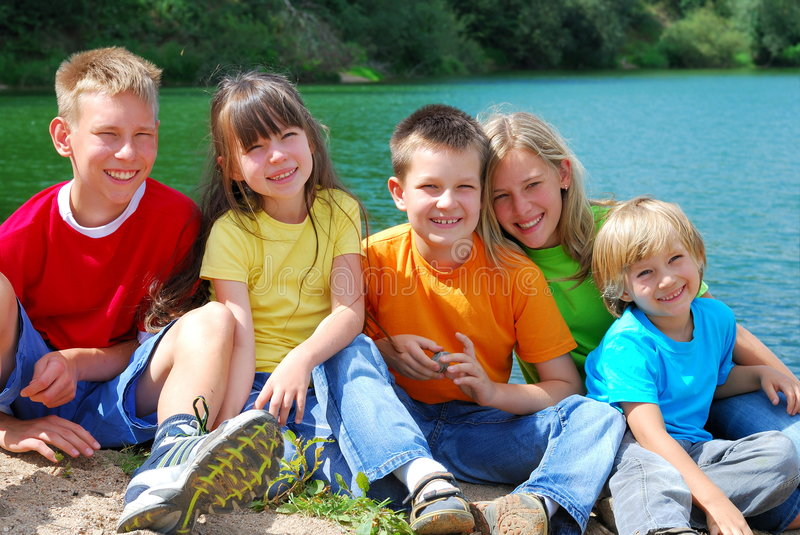 Children at the lake. Five happy children sit together at a lake, smiling