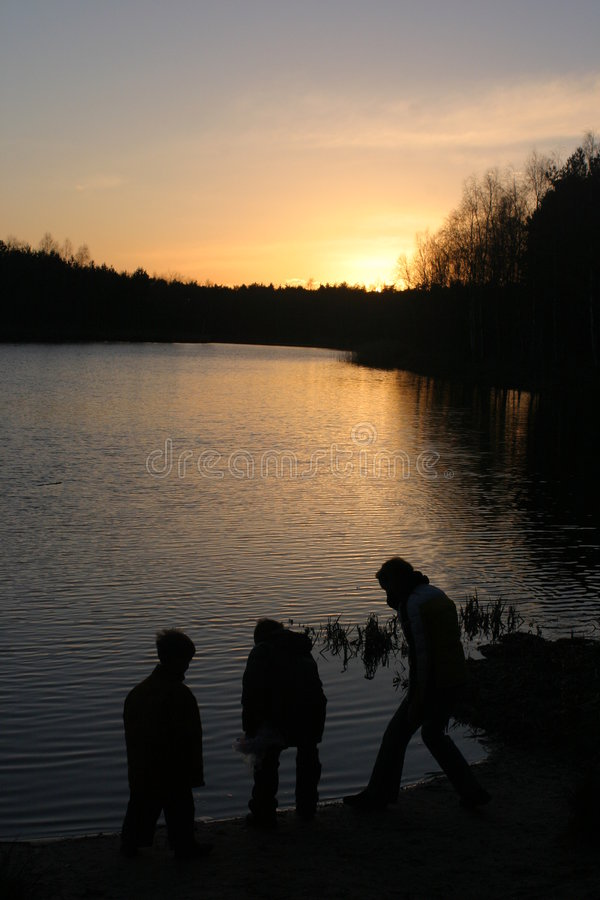 Children at a lake at sunset stock photography